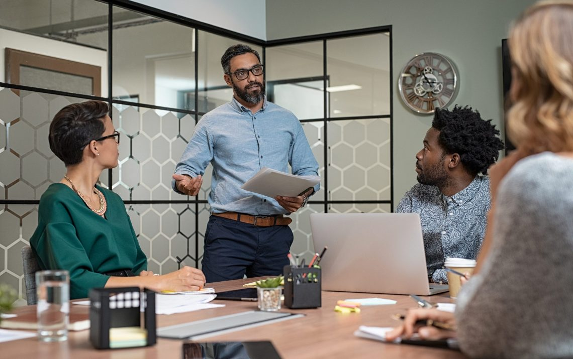 Confident mature businessman giving a presentation to his team i