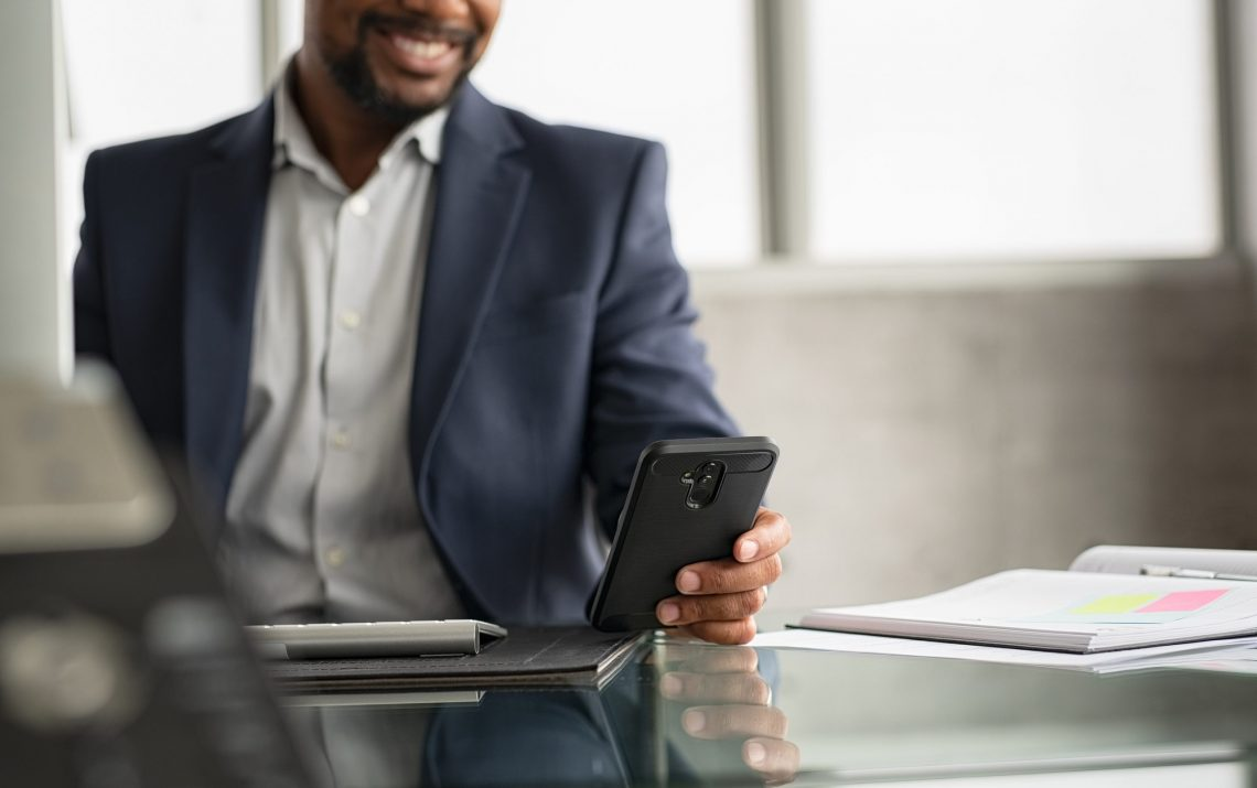 Detail of black manager sending phone message in a modern office. Closeup of african businessman hand checking cellphone. Smiling mature man using smartphone while working on desk at modern office.