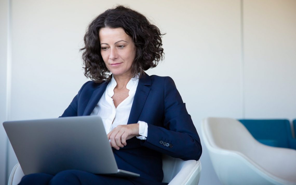 Focused Businesswoman Using Laptop In Office. Concentrated Middl