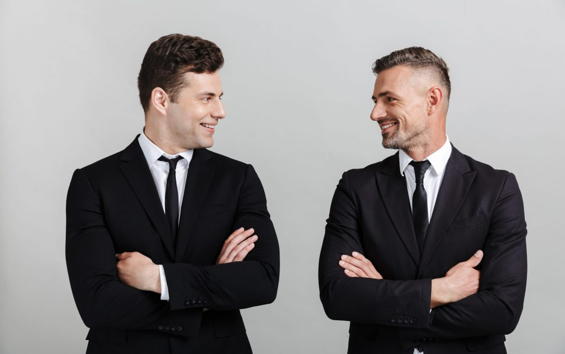 Two attractive confident businessmen wearing suits standing isol
