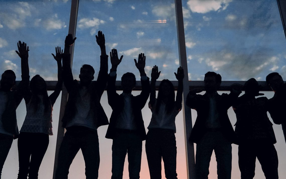 silhouette of a group of business people raising their hand